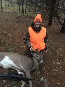 Katrina posing with an antlered deer she hunted.